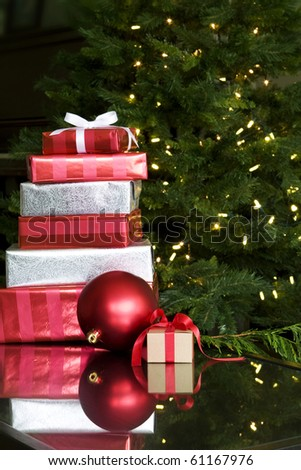 christmas presents with red bow on coffee table with xmas tree - stock photo