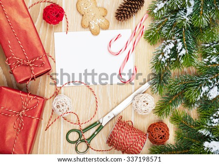 Christmas presents wrapping and snow fir tree over wooden table background with blank greeting card - stock photo