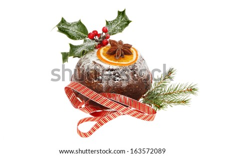 Christmas pudding decorated with seasonal foliage, star anise and orange with a ribbon isolated against white