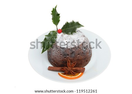 Christmas pudding on a plate decorated with holly and spices isolated against white