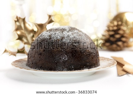 christmas pudding on table, with christmas decoration in background, shallow DOF - stock photo