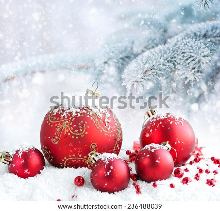 Christmas red balls on a background snow-covered fir branches - stock photo