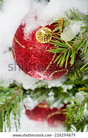 Christmas red balls on branch in snow - stock photo