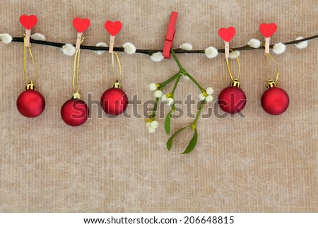 Christmas red bauble decorations with mistletoe leaf sprig hanging on a pussy willow branch over brown paper background. - stock photo