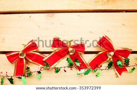 Christmas Red Bow ribbon over wooden texture background with copy space - stock photo