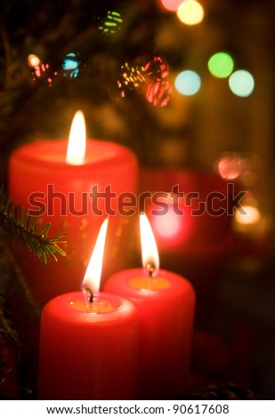 Christmas red candles with lights and fir-tree on the background