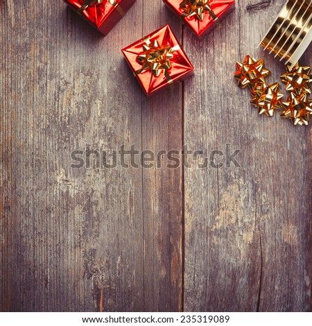 Christmas Red Gift Boxes with ribbon on rustic wood board - stock photo