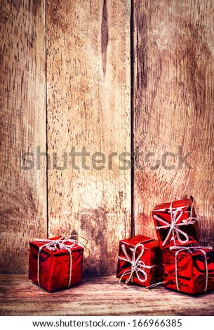 Christmas Red Gift Boxes with ribbon on rustic wood board with copy space for greeting text.  Festive decoration  over wooden background.  - stock photo