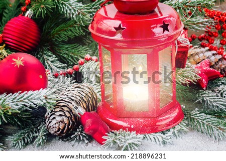christmas red glowing lantern close up  with evergreen tree and snow