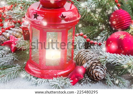 christmas red glowing lantern close up  with fir  tree and falling snow
