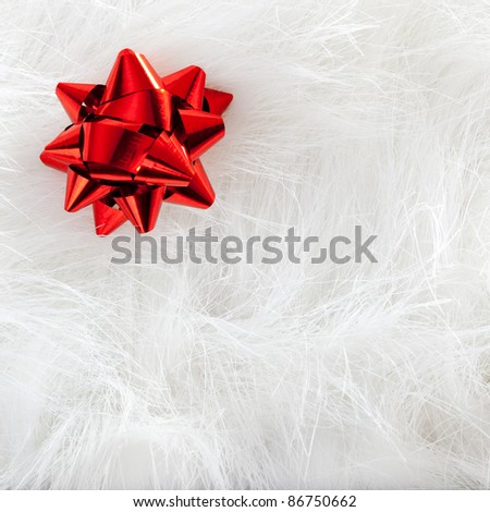 Christmas red ribbon look over white fur background - stock photo