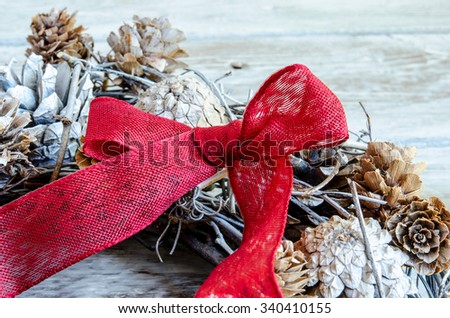 Christmas Red ribbon on leaves and branches - stock photo