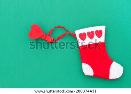 Christmas red sock made of felt on the clothespin in the form of heart on a green background - stock photo