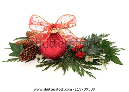 Christmas red sparkling bauble with glitter bow surrounded by holly, ivy, mistletoe and cedar leaf sprigs with pine cones over white background. - stock photo