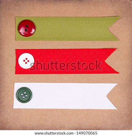 Christmas ribbon tags with buttons on scrapbook paper background - stock photo