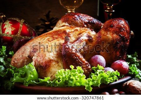 Christmas roast turkey or chicken decorated with nuts, fir cones, balls on the old wooden background, selective focus