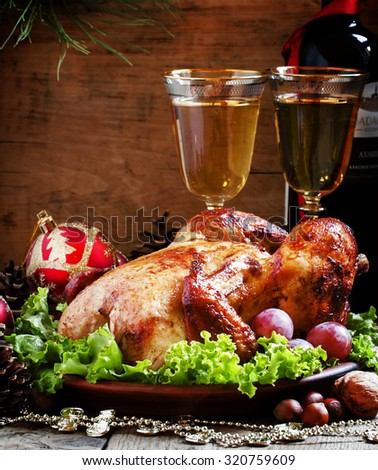 Christmas roast turkey or chicken decorated with nuts, fir cones, balls on the old wooden background, selective focus - stock photo