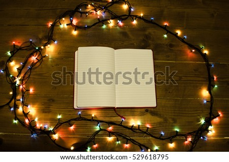 Christmas romantic lights frame on wooden background with open notebook.