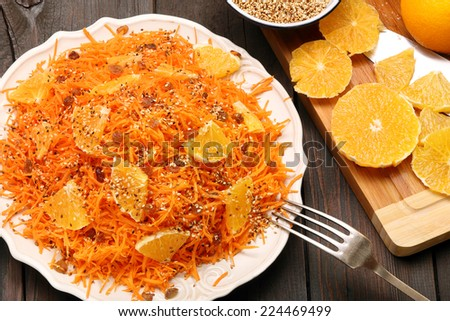 Christmas salad from carrots with orange, raisins and roasted sesame seeds on a wooden background - stock photo
