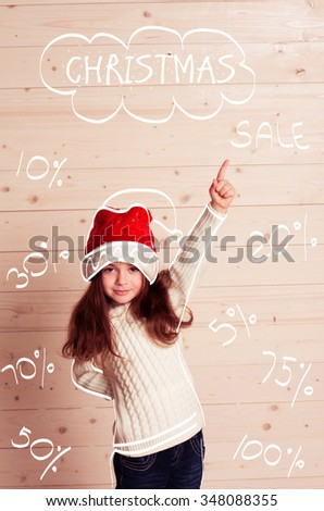 Christmas sale. Kid girl 4-5 year old showing by forefinger on Christmas sign. Discount. Enjoyment. 50, 70, 20,10, 5 percent off.