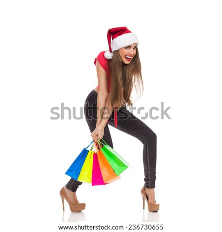 Christmas sale. Smiling christmas girl carrying heavy colorful shopping bags. Full length studio shot isolated on white. - stock photo