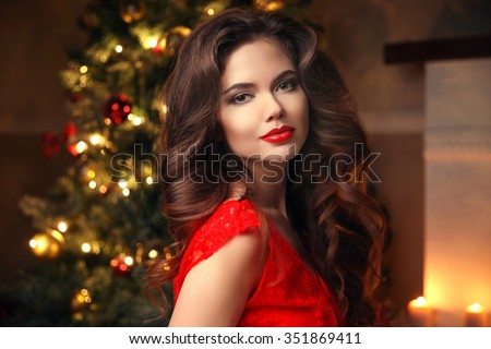 Christmas Santa. Beautiful smiling woman model. Makeup. Healthy long hair style. Elegant lady in red dress over christmas tree lights background. happy new year. - stock photo