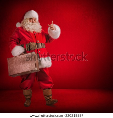 Christmas: Santa Claus Standing With Travel Bag with Gits on red background - stock photo