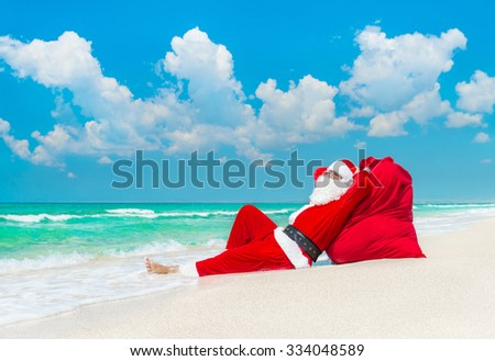 Christmas Santa Claus sunbathing at big sack full of gifts at ocean tropical sandy beach - xmas or New Year's travel vacation discounts and travel agencies price reductions concept - stock photo