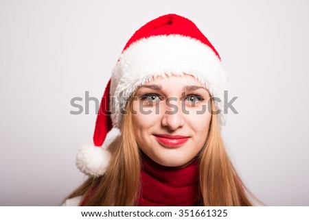 Christmas Santa hat isolated portrait of a girl. A smiling happy girl on a gray background - stock photo