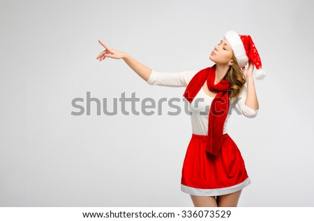 Christmas Santa hat isolated woman portrait . Pointing finger towards gray background. Girl in white and red clothes.