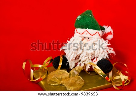 Christmas Santa puppet and the golden gift box with ribbon on red - stock photo