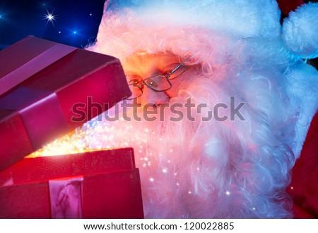 Christmas Santa. Santa Claus opening Magic Gift Box. - stock photo