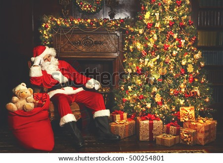 Christmas. Santa tired asleep in chair near Christmas tree and bag with gifts