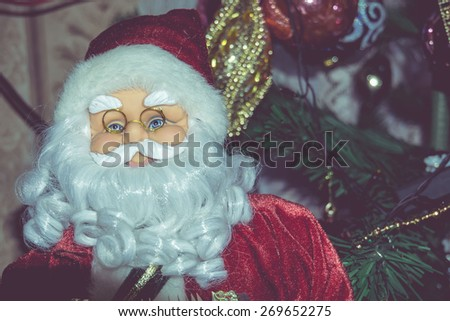 Christmas santa toy playing the accordion, vintage photo effect background. - stock photo