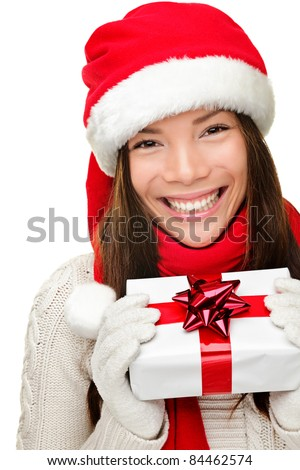 Christmas santa woman holding gift. Smiling happy cute young woman wearing santa hat showing christmas present isolated on white background. Joyful mixed race Asian Caucasian santa girl. - stock photo