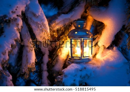 Christmas scene - an oil filled lantern burning bright with snow covered tree