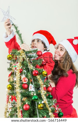 Christmas scene at home. Single mother and son setting up the Christmas tree.Small Hispanic family - stock photo