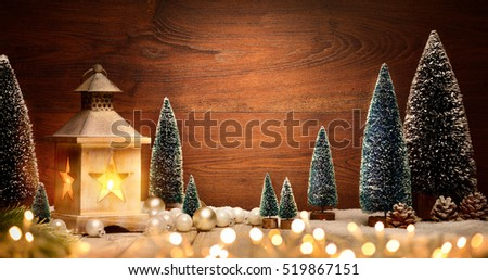 Christmas scene with a lantern, trees, baubles and blurred lights in front of an illuminated elegant dark wooden board as copy space