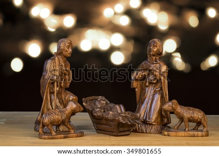Christmas scene with figurines. Baby Jesus, Mary, Joseph on light bokeh background. - stock photo