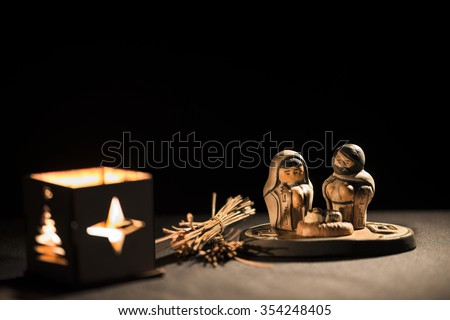 Christmas scene with figurines including Jesus, Mary and Joseph on a black backgrond - stock photo