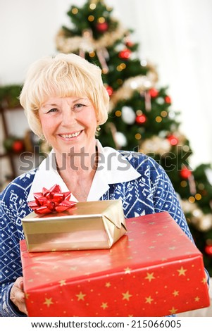Christmas: Senior Woman Stands With Wrapped Gifts - stock photo