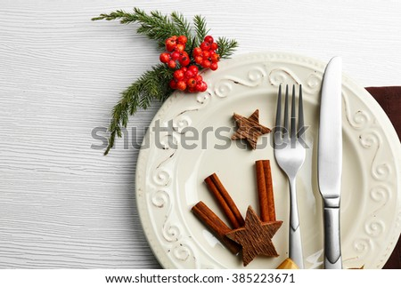 Christmas serving cutlery on plate over light wooden table, close up - stock photo
