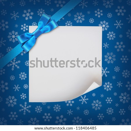 Christmas sheet of paper with blue ribbon bow on blue snowflakes background - stock photo