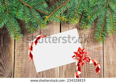 Christmas Sheet Of Paper With Bow And Christmas Fir Tree On A Wooden Background - stock photo