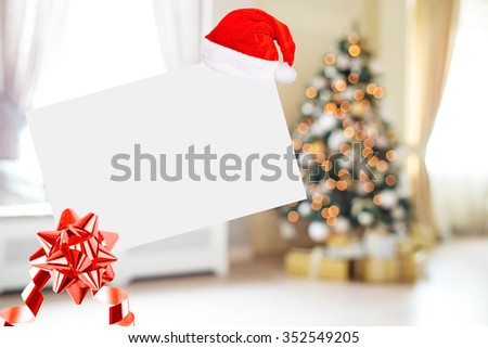 Christmas Sheet Of Paper With Bow And Santa Hat On Defocused background Living room with christmas tree - stock photo