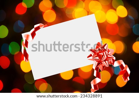 Christmas sheet of paper with bow on yellow and blue defocused background - stock photo