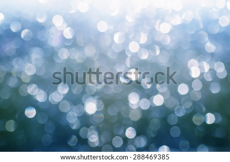 Christmas shiny glitter light bokeh in  blue silver colors, seasonal holiday blurred background - stock photo