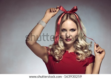 christmas shoot of funny blonde girl with pois bow on her head, adorned like a xmas gift, wearing elegant red dress and bracelet   - stock photo