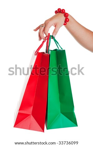Christmas shopper with red and green shopping bags.  Shot on white background. - stock photo