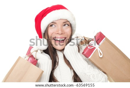 Christmas shopping advertisement woman thinking looking up at copy-space. Isolated head and shoulder portrait of shopper with gift bags. White background. - stock photo